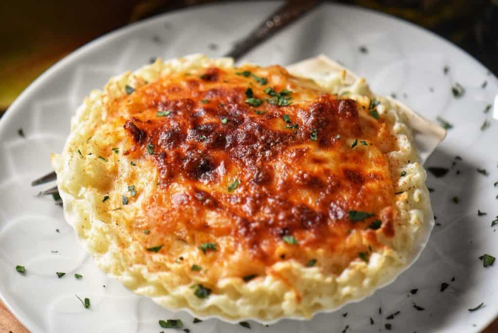 A golden cheesy crust of Coquilles St-Jacques.