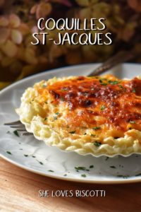 A single serving of Coquilles St-Jacques on a white plate.