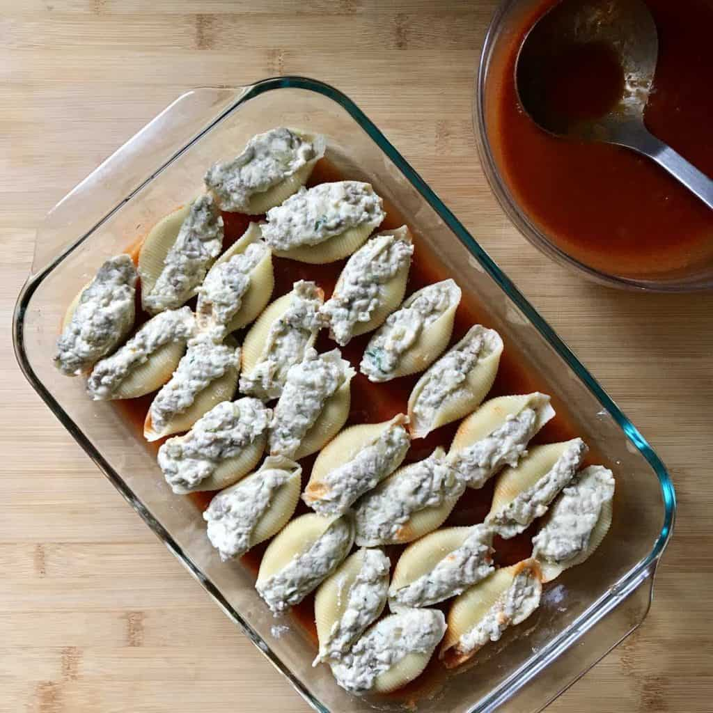 The filled pasta shells in a baking dish.