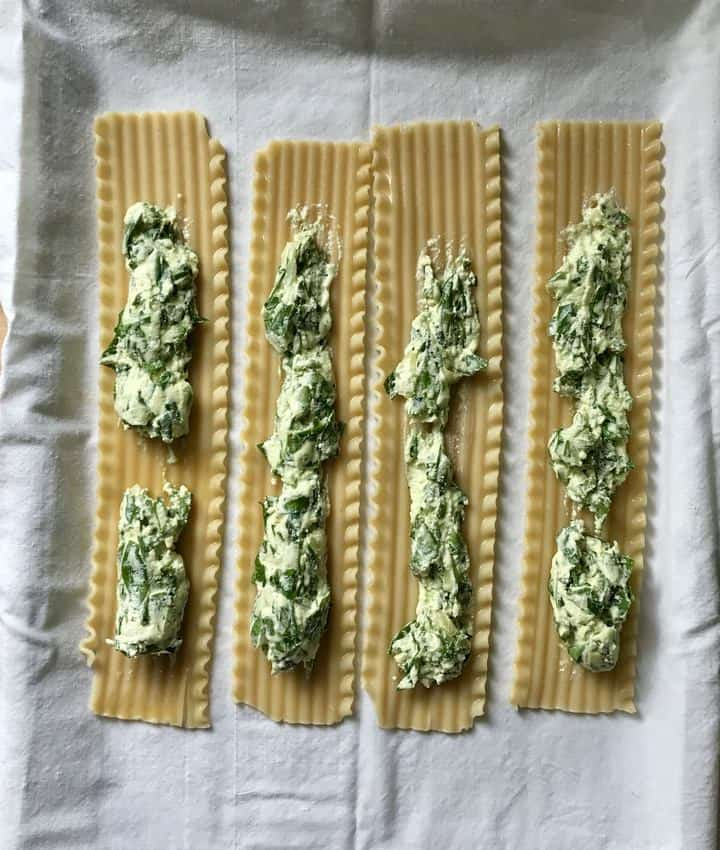 The spinach ricotta cheese mixture is spread on the lasagna noodles.