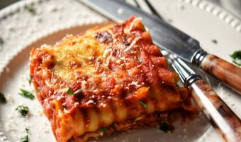 The cheesy top of a lasagna roll up on a white ceramic dish.