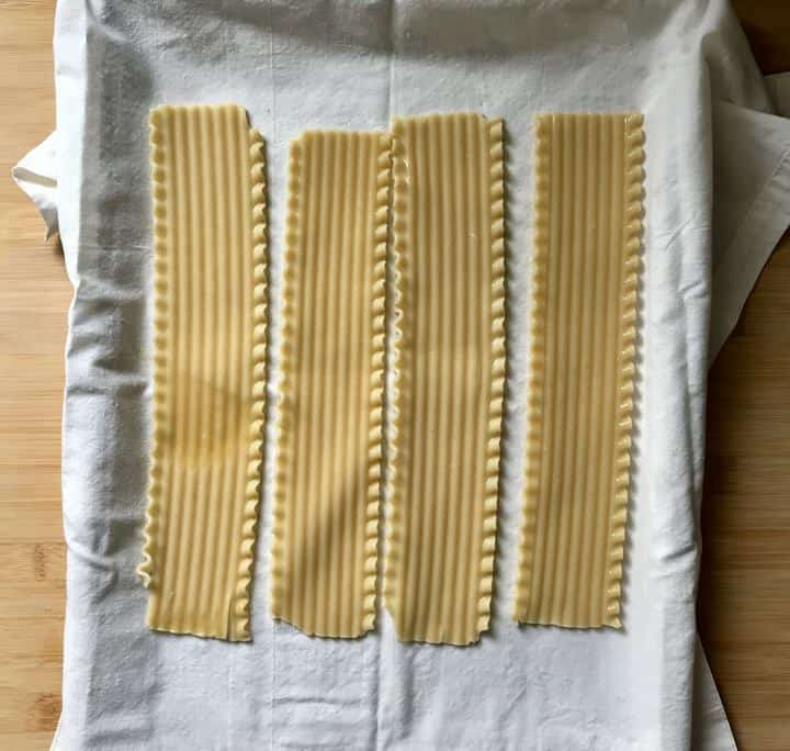 Lasagna noodles on a white tea towel.