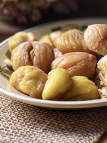 Boiled and peeled chestnuts on a serving dish.