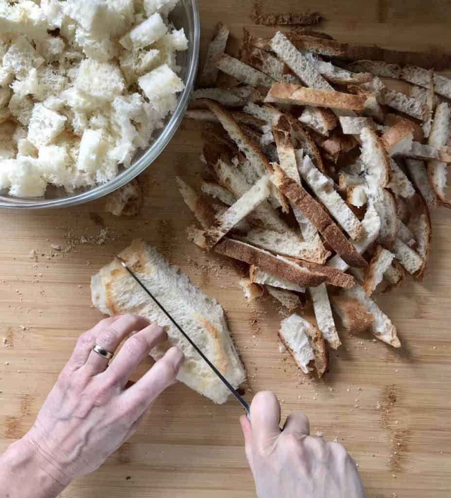 The crusts are being removed form a country style bread.