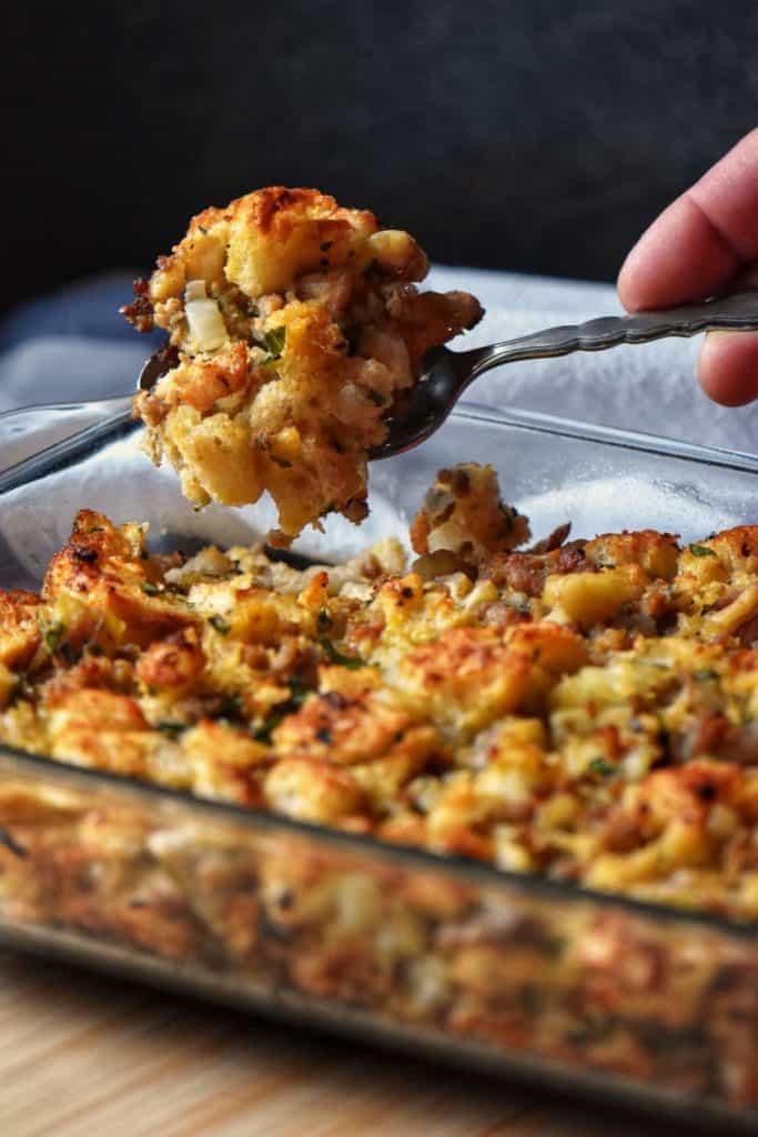 A portion of chestnut stuffing being lifted from the baking dish.