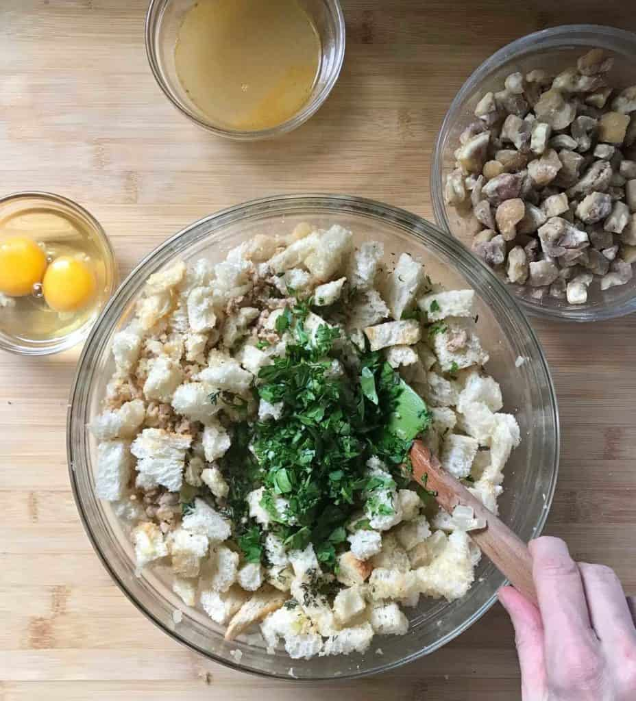 Parsley, sage and thyme added to the chestnut stuffing in a bowl.