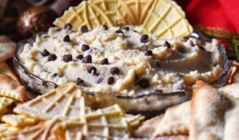 Cannoli dip in a serving dish surrounded by pizzelle.