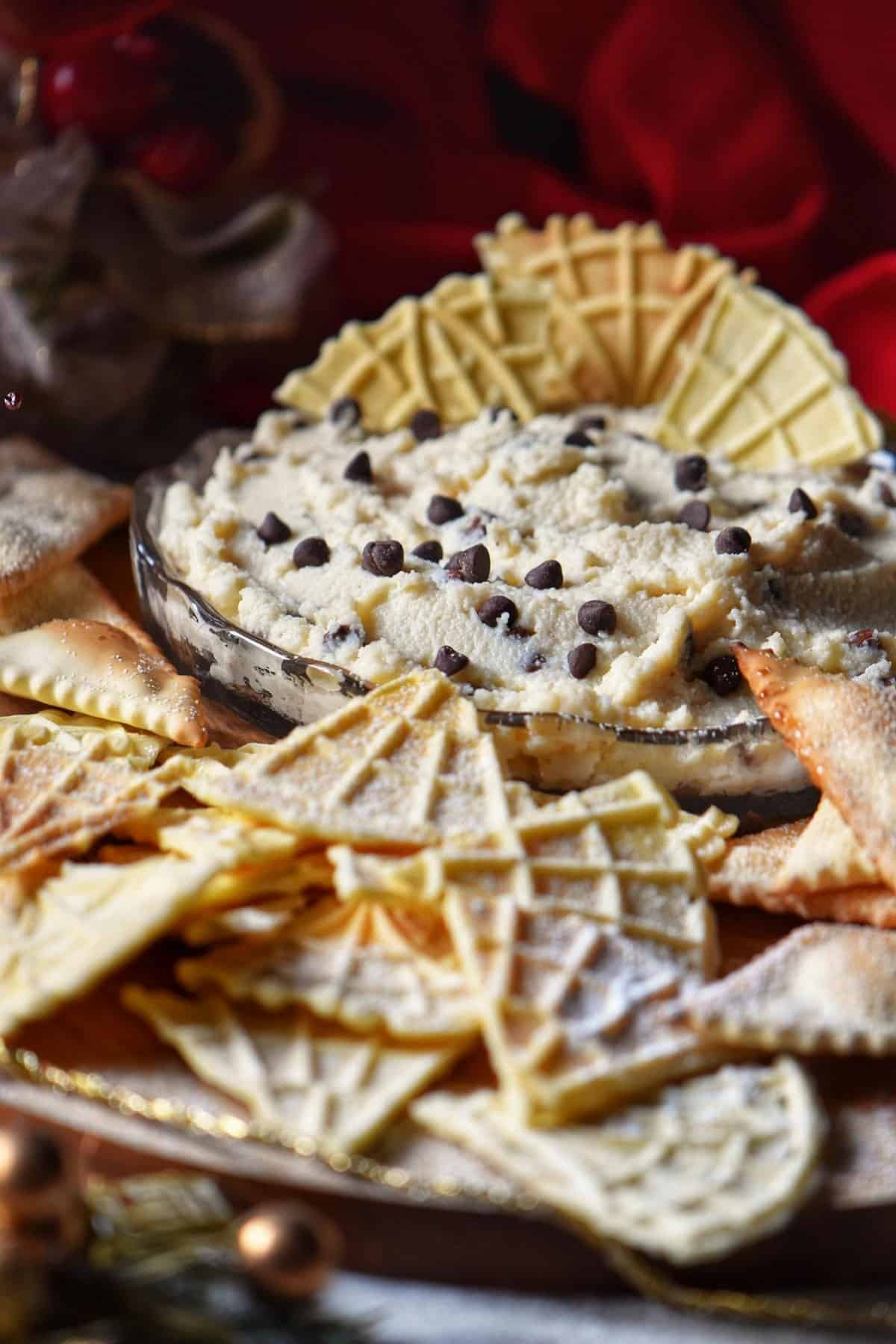 Cannoli Dip surrounded by pizzelles and air fryer Italian cookies.