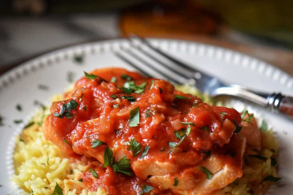 Cod fish smothered in tomato sauce, on a white dinner plate.