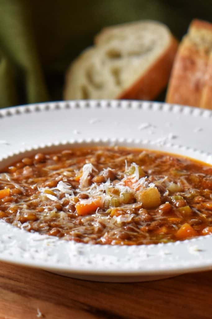 Close up of grated cheese on lentil soup.