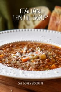 Lentil soup in a white bowl garnished with grated cheese.