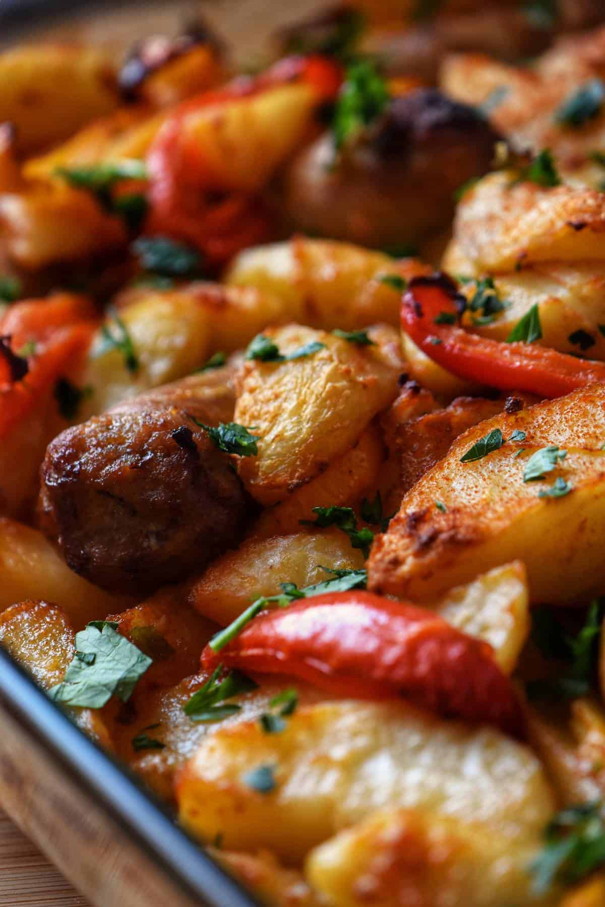 Roasted sausages and vegetables in a baking dish.