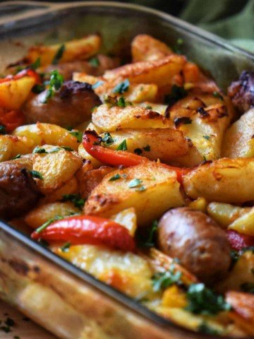 Italian Sausage, Potatoes, Peppers, and Onions in a baking dish.