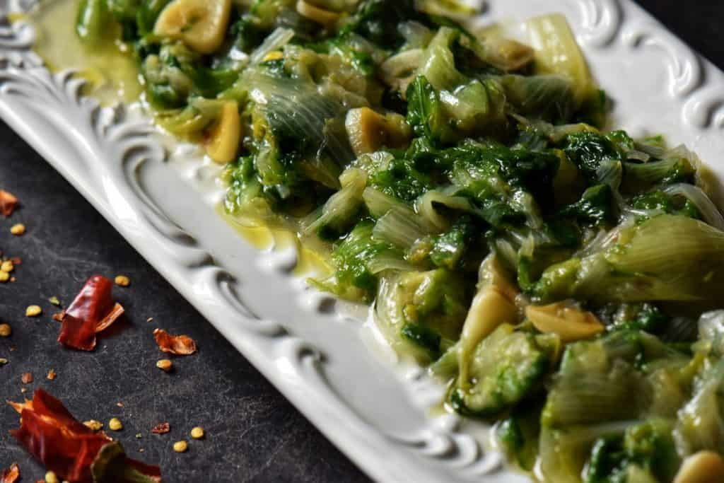 Cooked greens in a white serving dish.