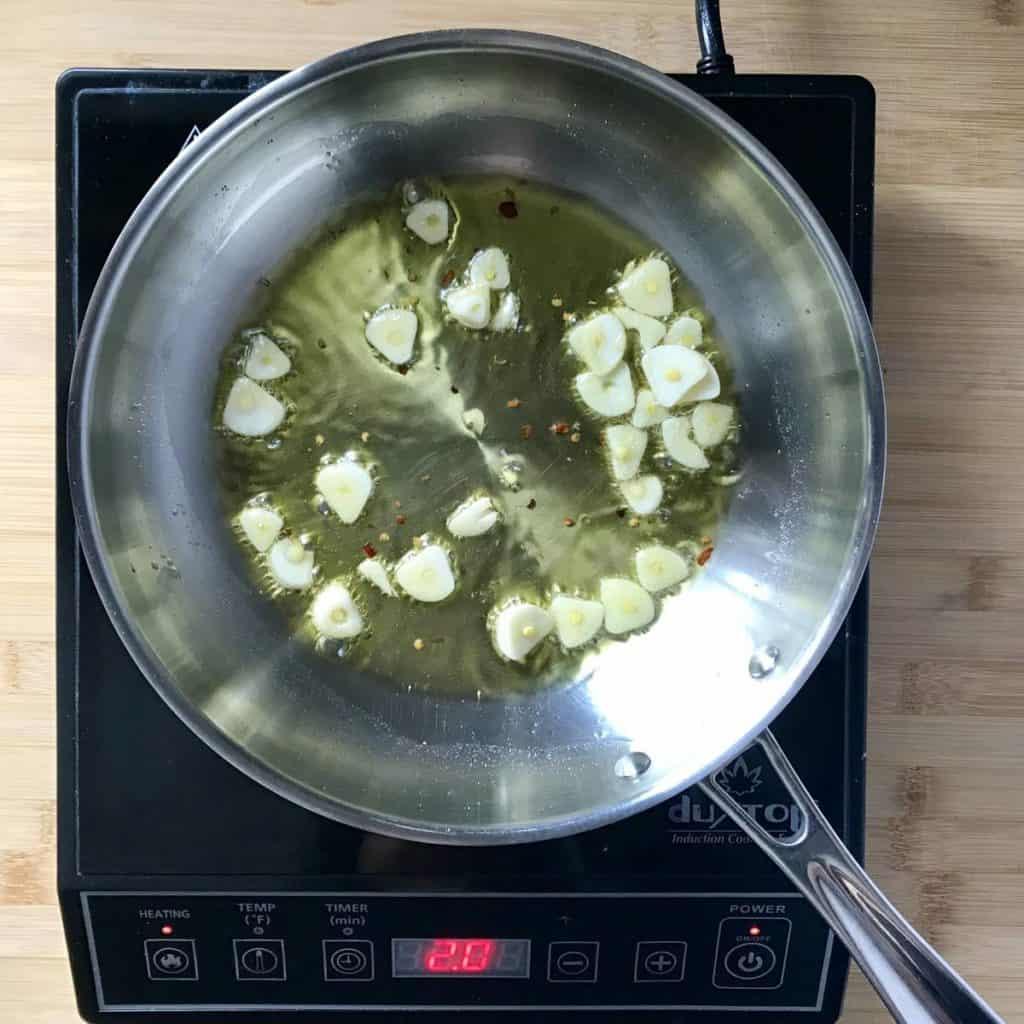 Sliced garlic sauteed in a pan.