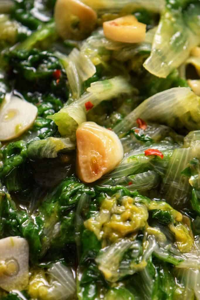 A close up photo of escarole with garlic.