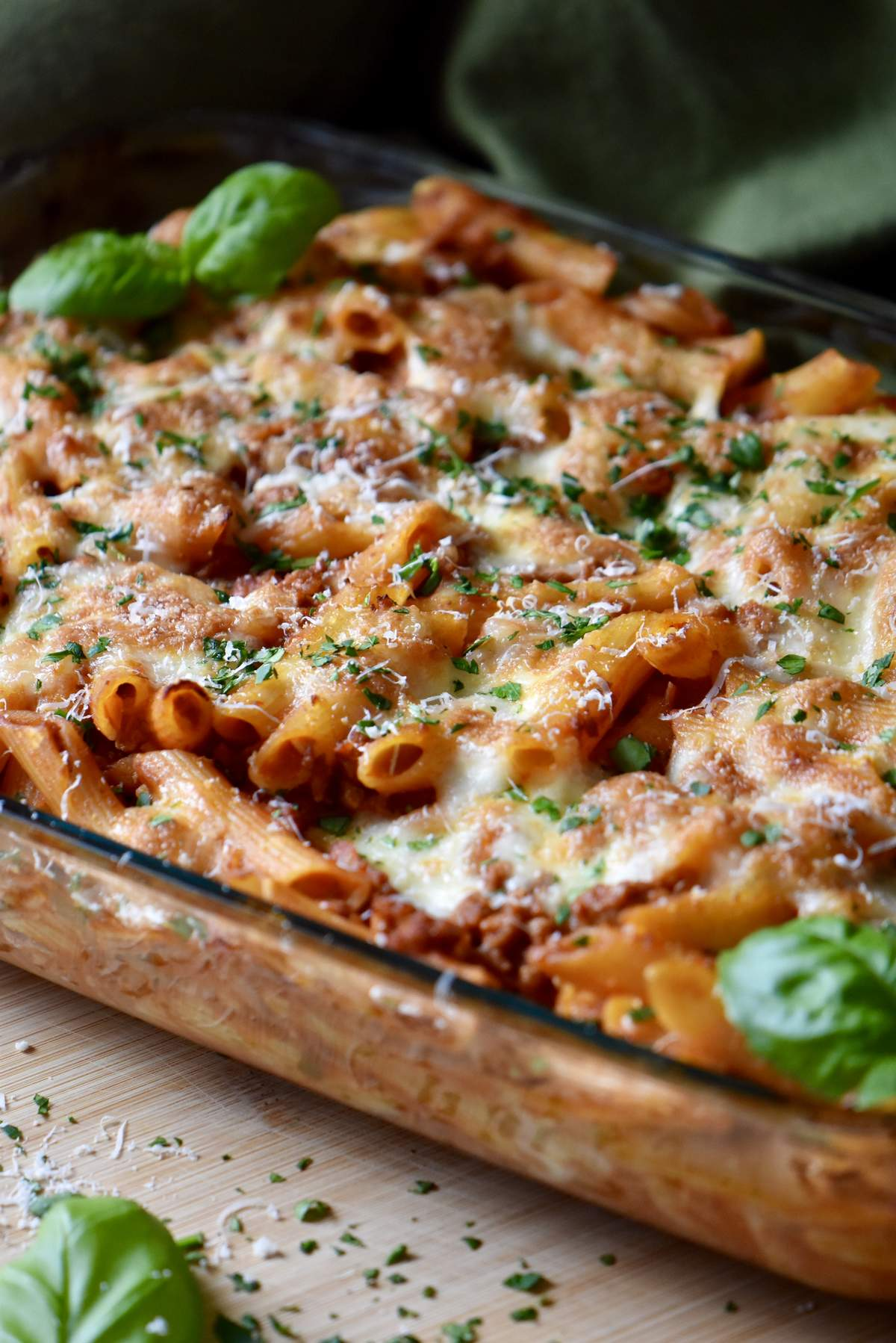 Basil leaves top a cheesy baked pasta dish.