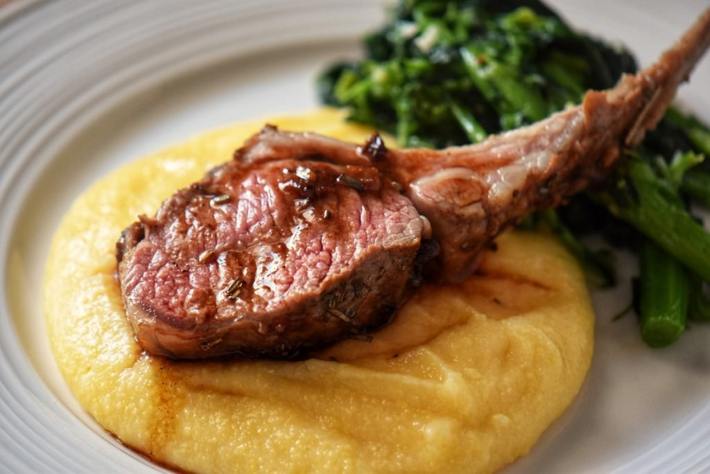 A single lamb rib roast set over creamy polenta in a white dinner plate.