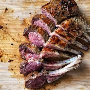 A rack of lamb on a wooden board.