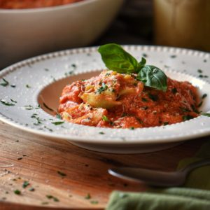Tortellini with ricotta tomato sauce in a white dish.