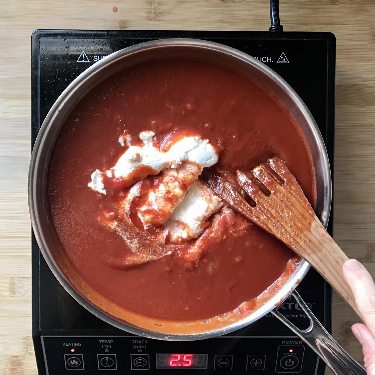 Ricotta cheese is added to tomato sauce in a saucepan.