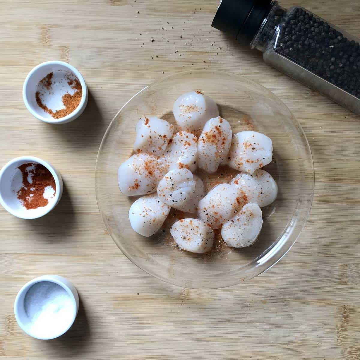 Spices and scallops on a wooden board.