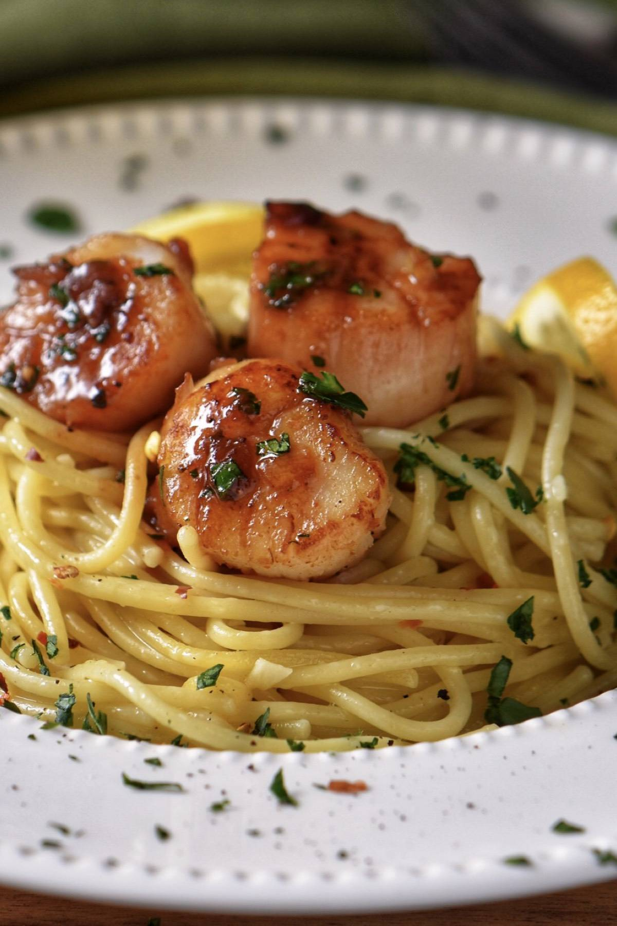 Pan seared scallops placed on pasta in a white bowl and garnished with parsley.