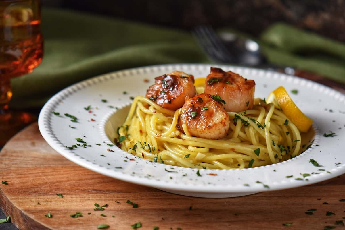 Pan seared scallops on spaghetti in a white plate.