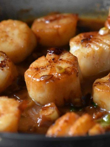 Pan seared scallops basted with the white wine sauce.