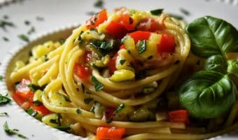 A plate of spaghetti topped with sauteed vegetables in a white plate.