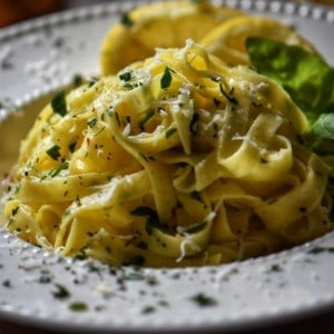 A white dish of fettuccine, garnished with chopped parsley.