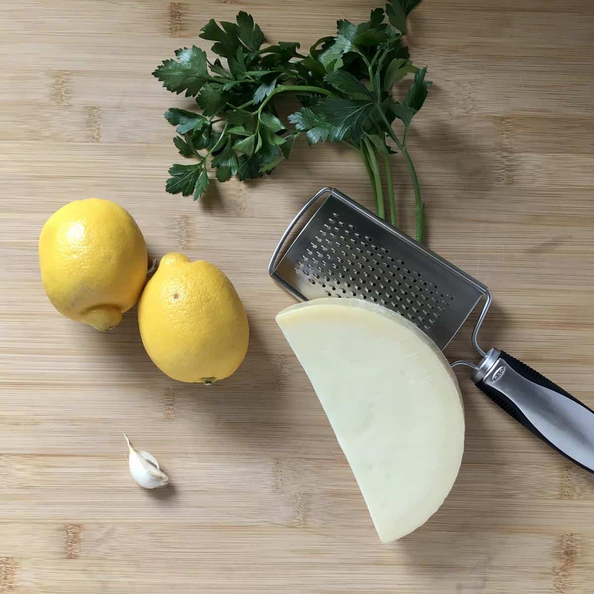 Garlic, lemons, parsley and cheese on a wooden board.