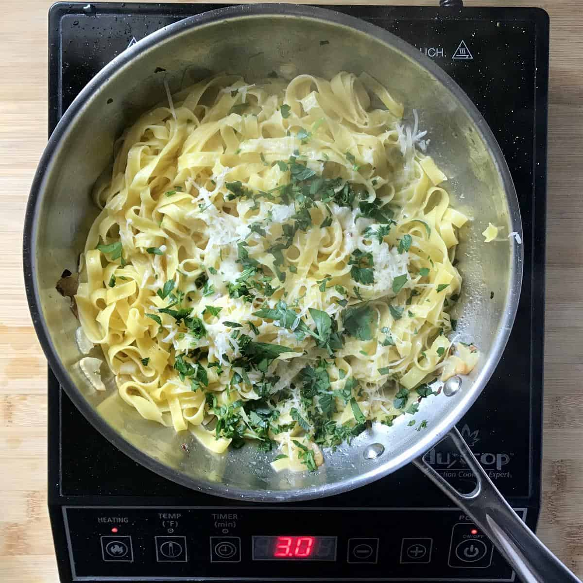 Chopped Italian parsley and grated cheese added to a pan of pasta.