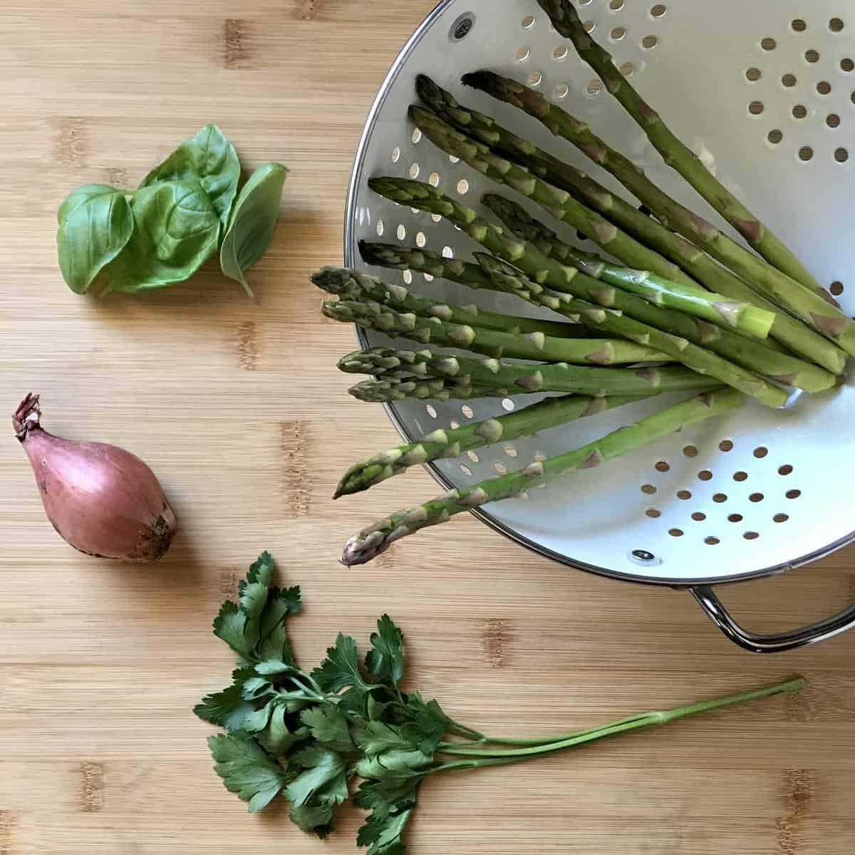 Asparagus, parsley, basil and a shallot on a cutting board.