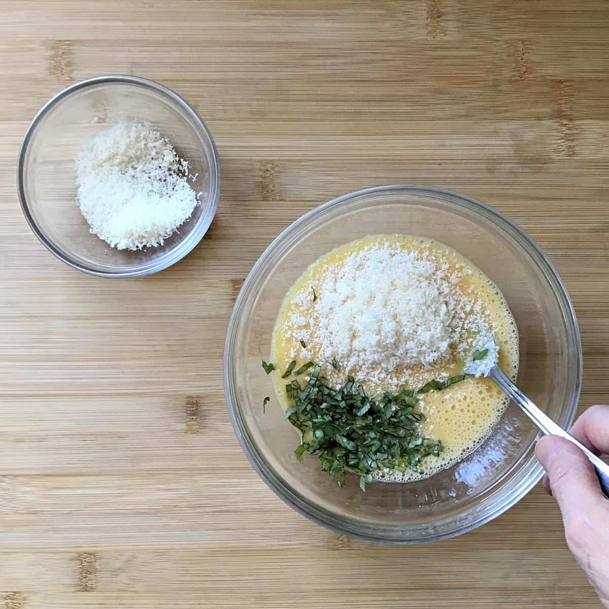 Grated cheese and fresh herbs added to eggs in a bowl.