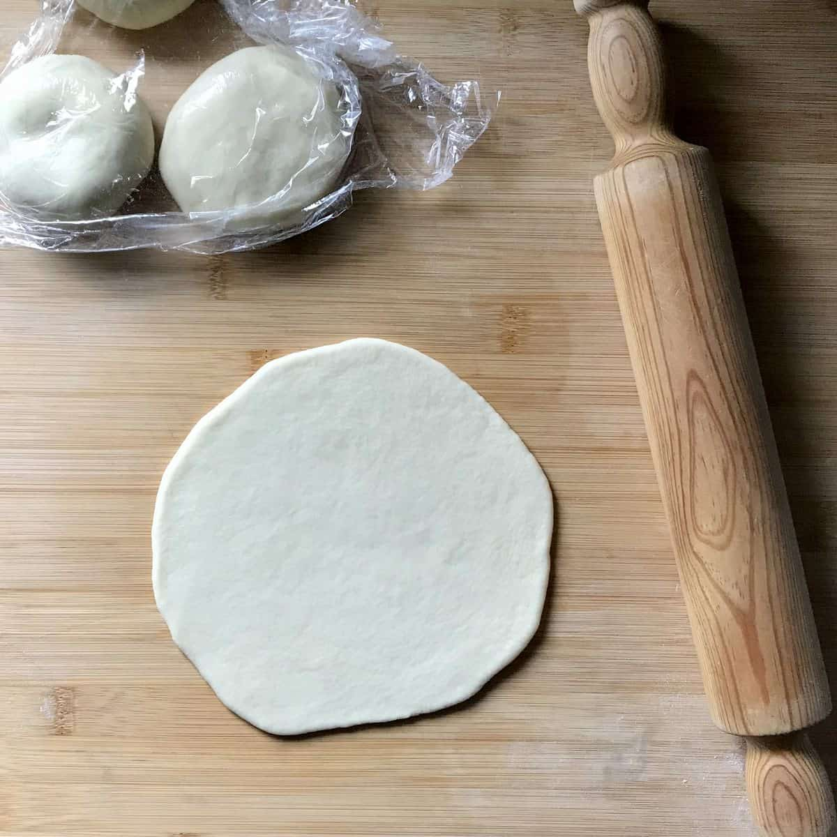 A rolled out piada on a wooden board next to a rolling pin.