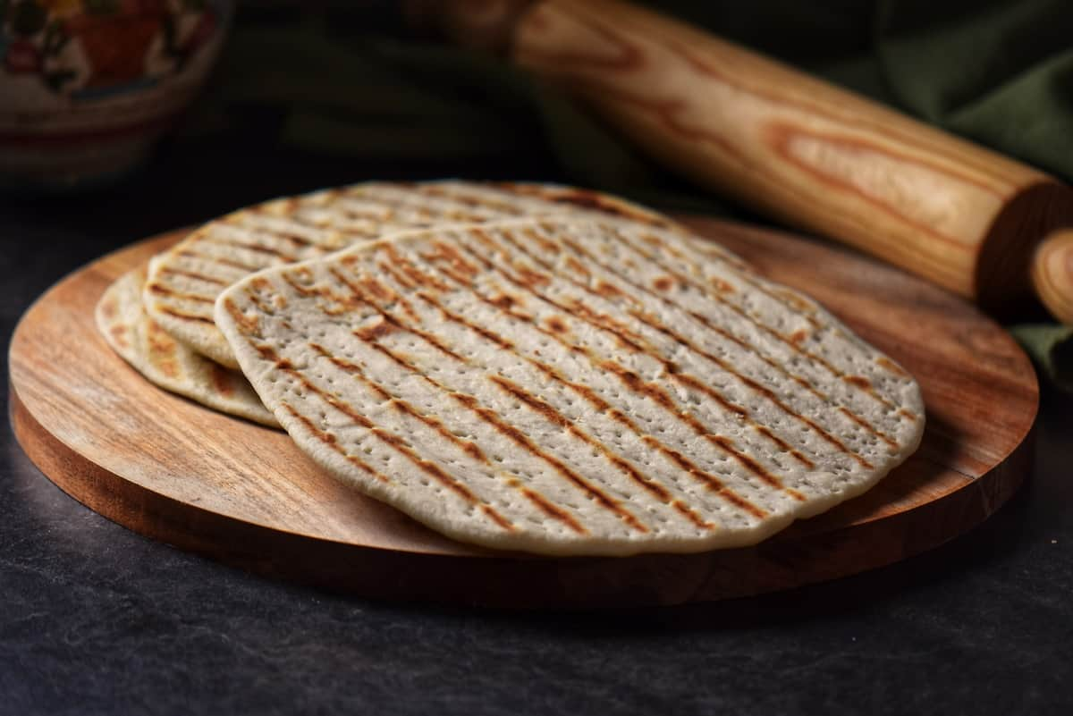 Grilled piadina set on a round wooden board.