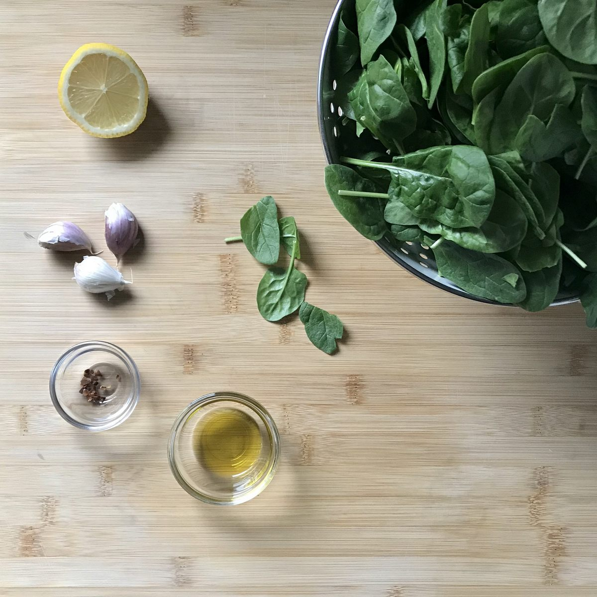 Ingredients to make sauteed spinach on a wooden board.
