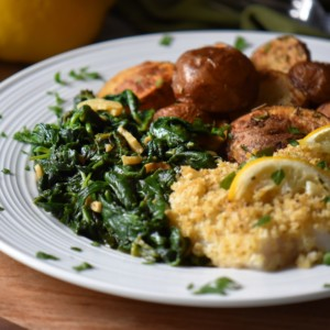 A white dinner plate with cod fish, air fried potatoes and a side dish of sauteed spinach.