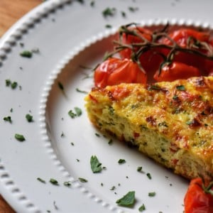 A slice of zucchini frittata in a white dinner plate.