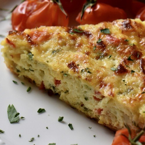 A slice of Italian zucchini frittata in a white dinner plate garnished with chopped parsley.