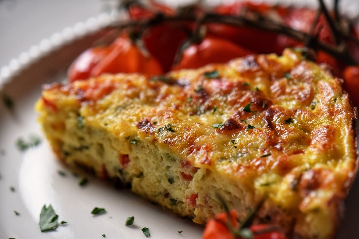 A zucchini and red pepper frittata in a white plate.