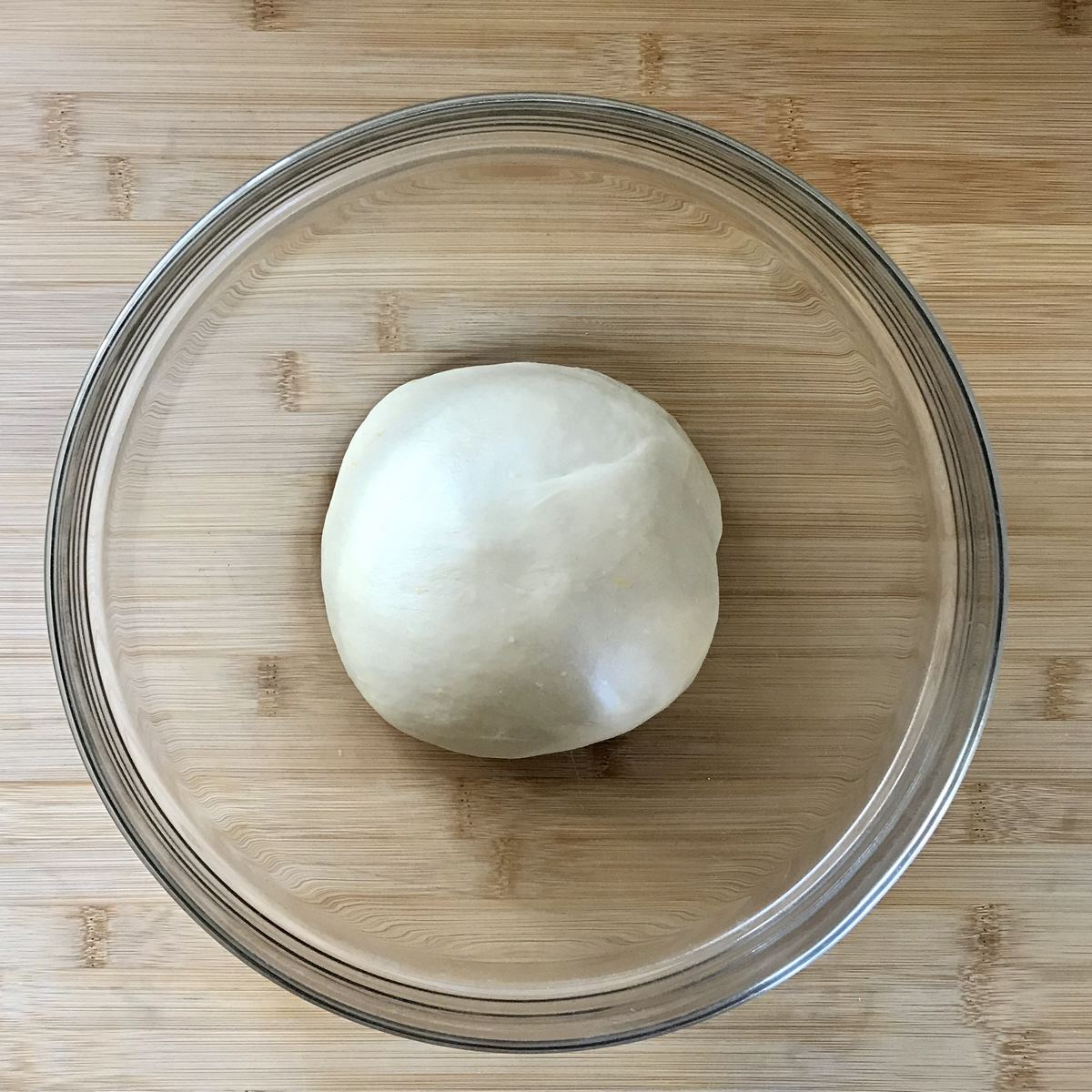 Ball of dough resting in a large bowl.