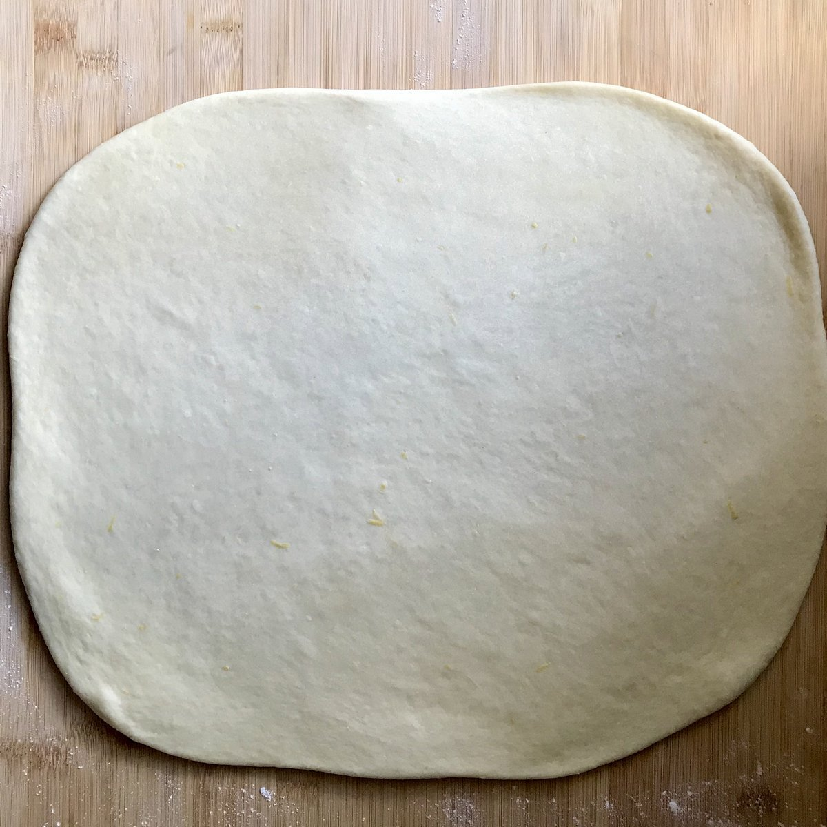 Stretched out dough on a wooden board.