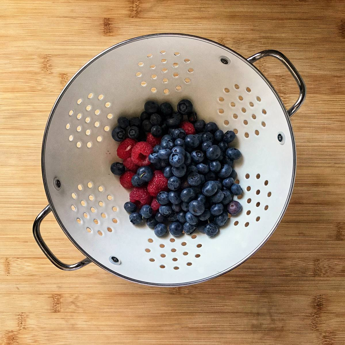Fresh blueberries ans raspberries in a white colander.