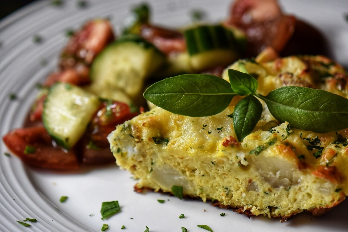 A slice of potato frittata in a white plate served with Italian tomato cucumber salad.