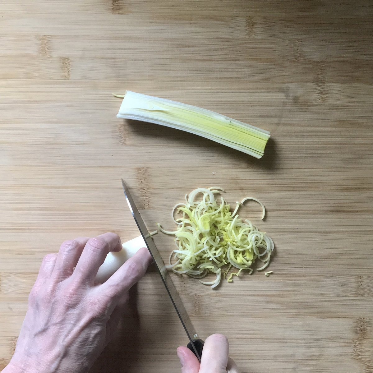 The white part of one leek in teh process of being chopped.