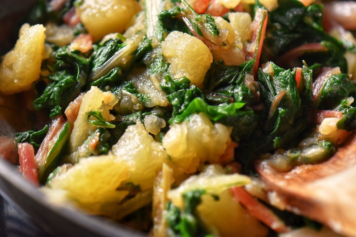 A close up photo of cooked Swiss chard mixed with potatoes.