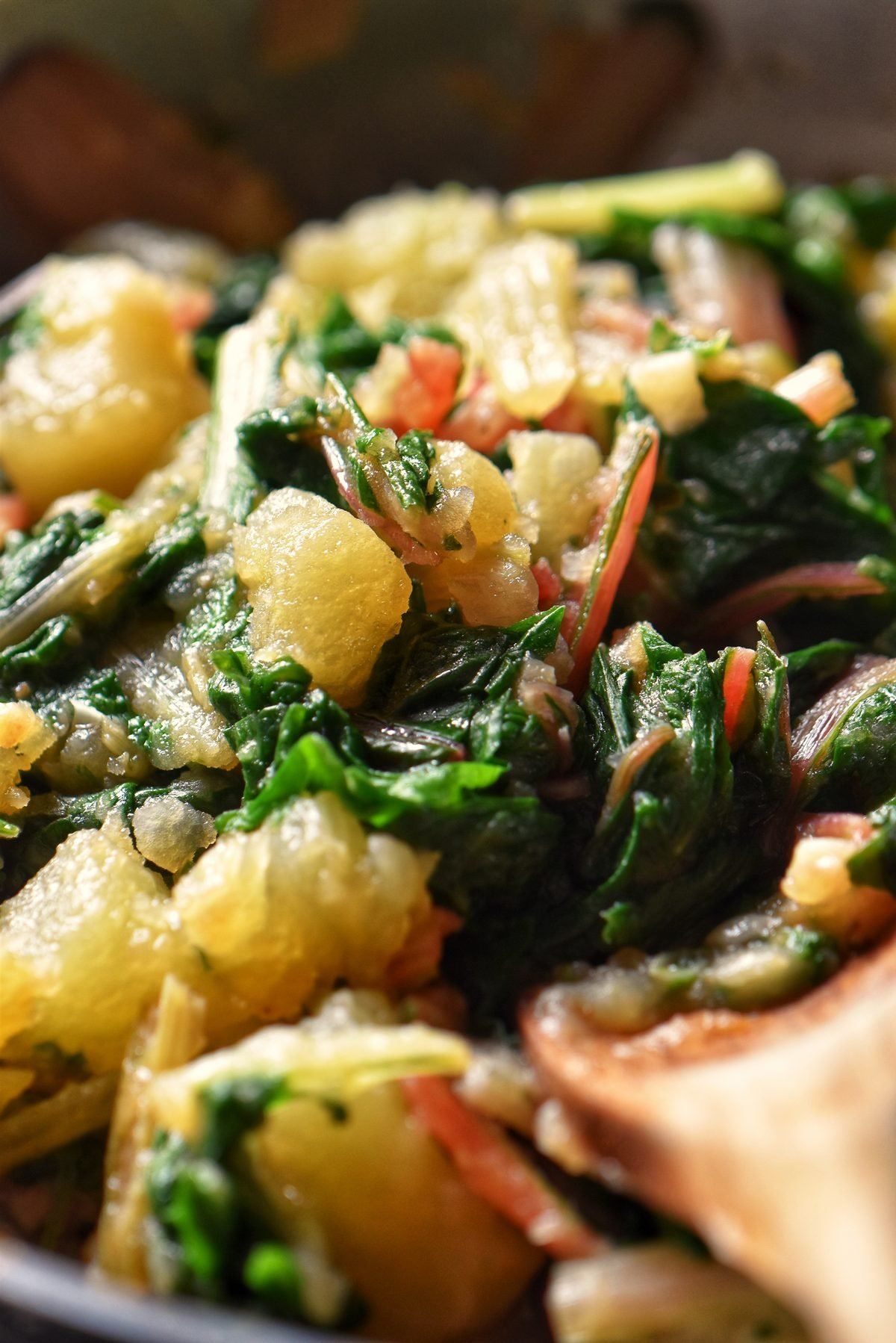 Potatoes and Swiss chard being sauteed together.