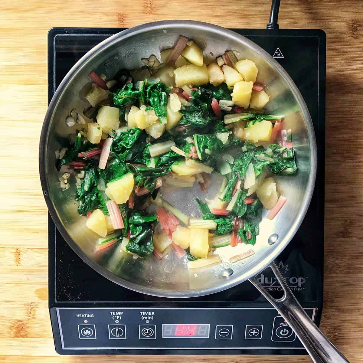 Swiss chard and potatoes in a pan.
